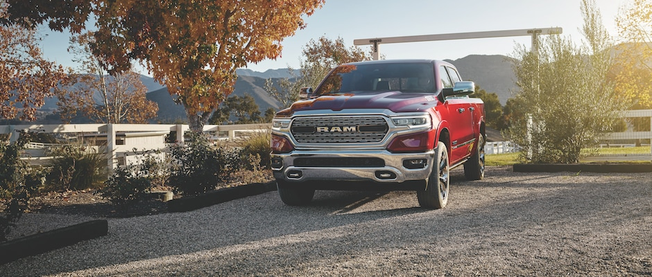 A red 2019 Ram 1500 driving onto a farm