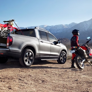 A silver 2019 Honda Ridgeline parked on the edge of a hill with one motor bike strapped in the truck bed and one motor bike parked beside the Honda truck with the rider looking into the distance at the snowy mountain range;