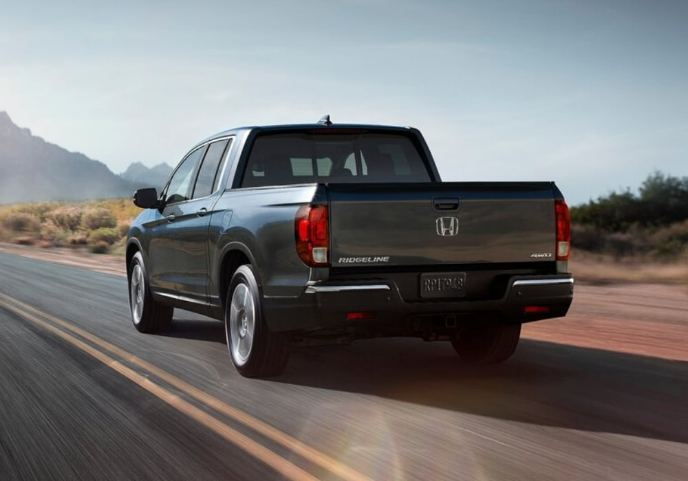 Ground level rear exterior view of a 2020 Honda Ridgeline driving toward the mountains