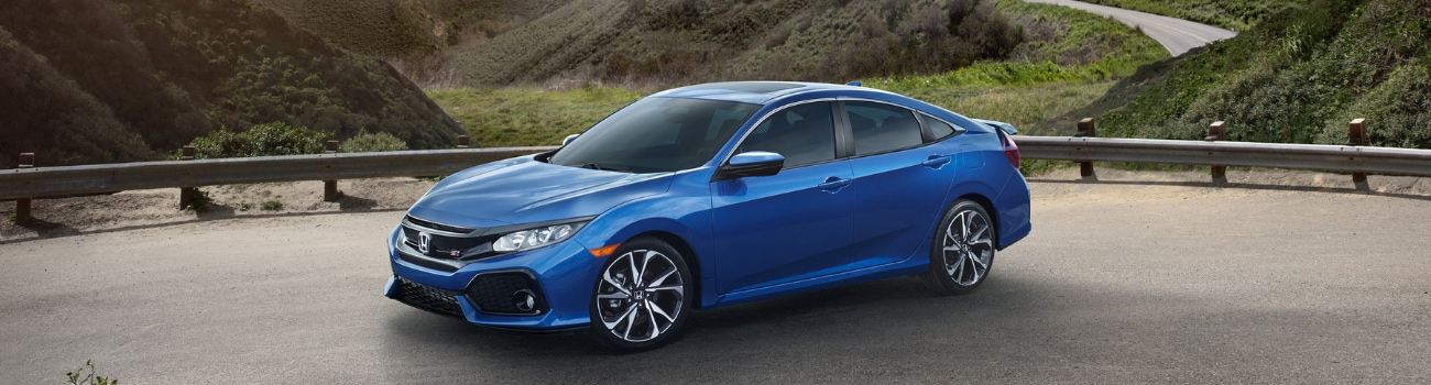 Look at the passenger side of a blue 2019 Honda Civic parked on the edge of a cliff overlooking grassy mountains that fall off into a distant ocean