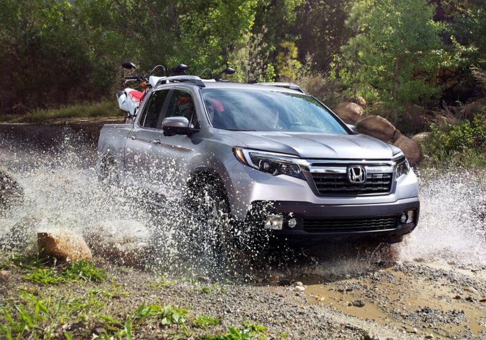 A 2020 Honda Ridgeline with two dirt bikes strapped down in the truck bed powering through a shallow river crossing in a green forest