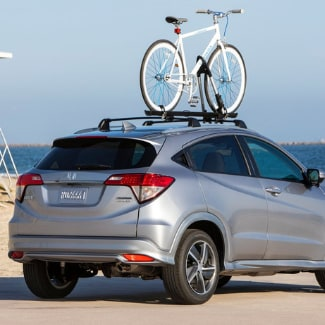 A silver 2019 Honda HR-V parked on a sandy road near the beach shore with a Honda bicycle mounted on top and a life guard stand with ocean waves in the background;
