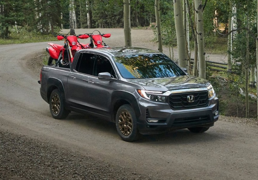 A new shiny 2021 Honda Ridgeline hauling two dirt bikes through a dirt off-road forest trail