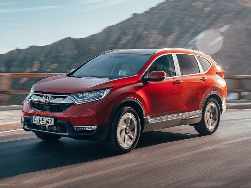 Front exterior of a red 2019 Honda CR-V driving through a mountain pass highway