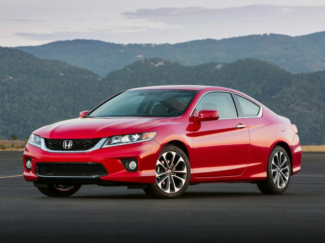 Driver side angle of a red Honda Accord coupe parked on asphalt with a mountain range in the background