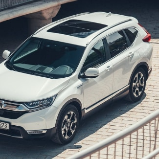 An aerial view of a white 2019 Honda CR-V taken from the balcony of a walkway overlooking the brick road where the car is parked;