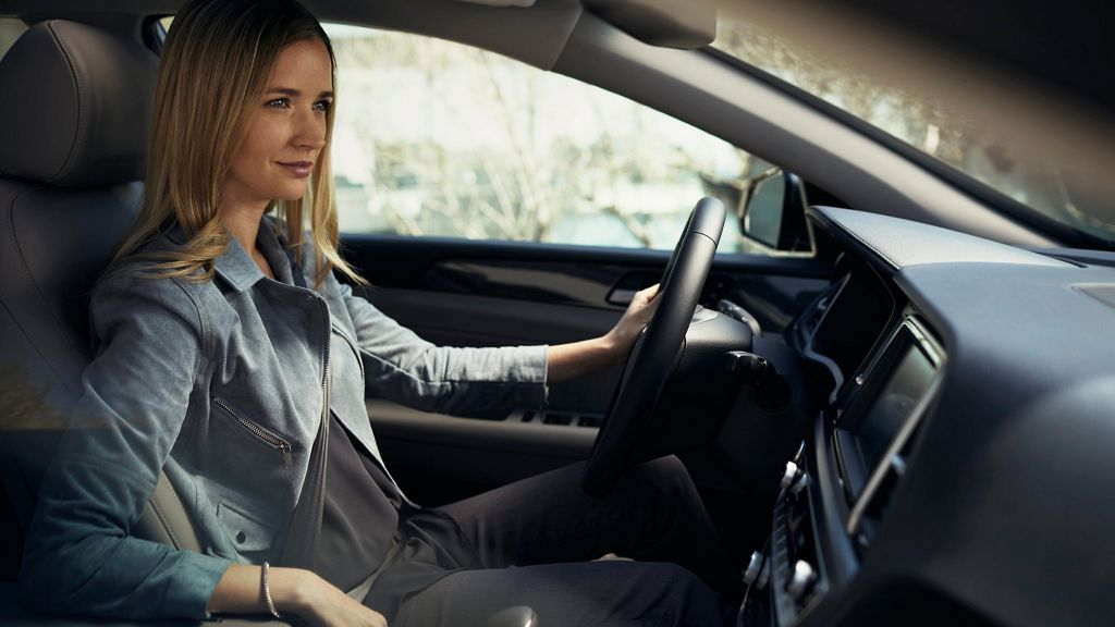 Happy woman sitting inside a new Hyundai>