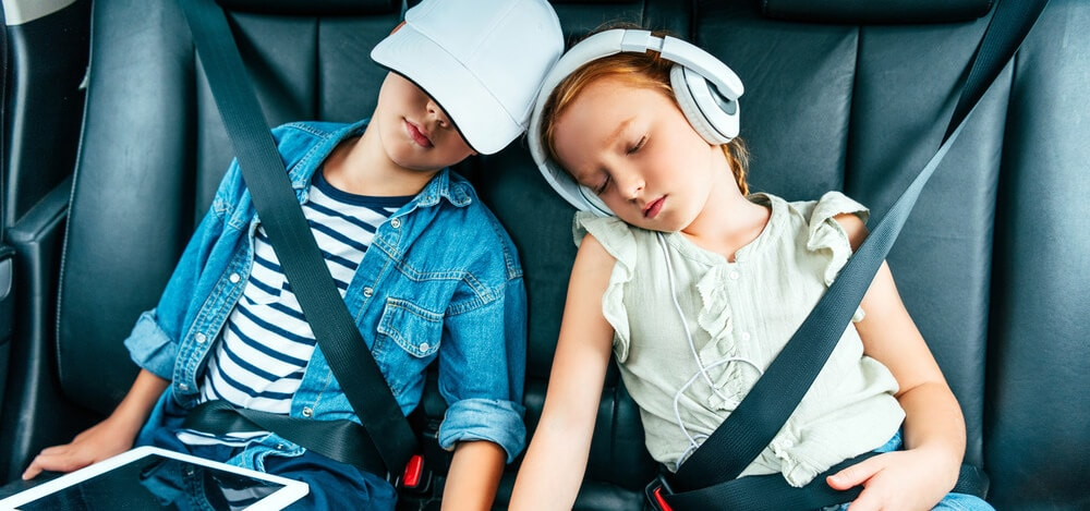 Exhausted children with digital devices sleeping in car during trip
