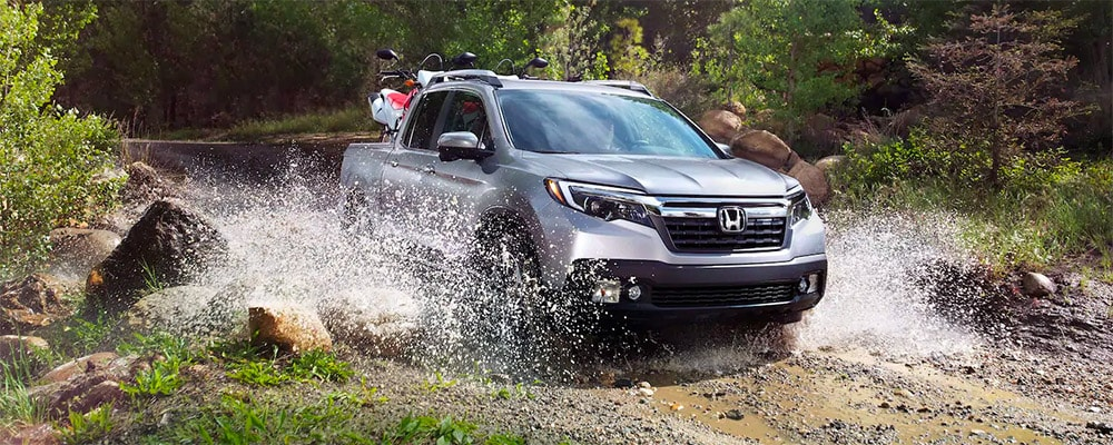 2019 Honda Ridgeline with ATV in the back splashing in the water