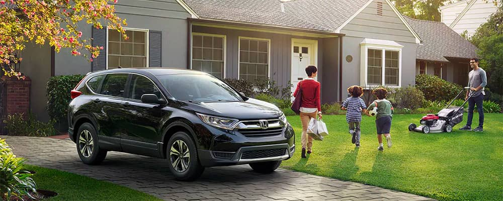 2019 Honda CR-V outside of house with family and Honda lawnmower