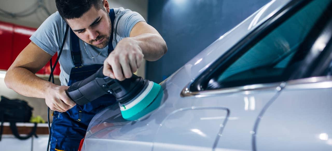 man polishes car with wax