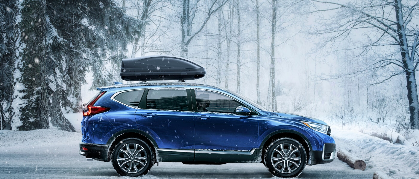 2020 Honda CR-V in Blue parked in snowy parking lot in the forest