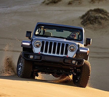 Silver Jeep Wrangler Driving on Sand