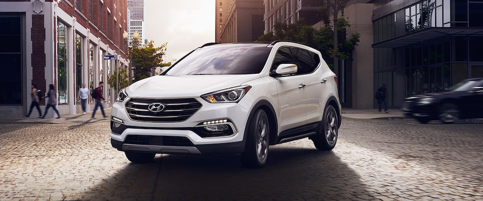 A white 2018 Hyundai Santa Fe parked on a cobblestone street in the middle of the city