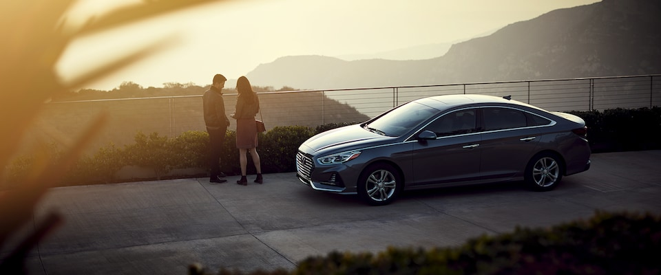 A couple watching a sunset by their Hyundai Sonata