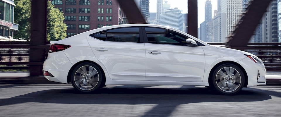 Exterior side shot of a white 2019 Hyundai Elantra driving downtown