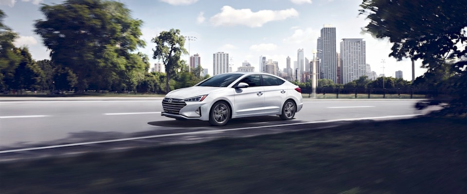 Exterior shot of a white 2019 Hyundai Elantra driving along the road