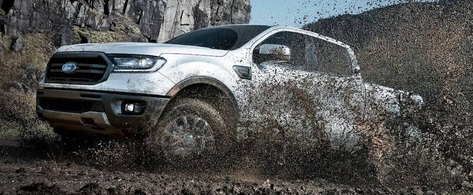 A white Ford Ranger Offroading through mud