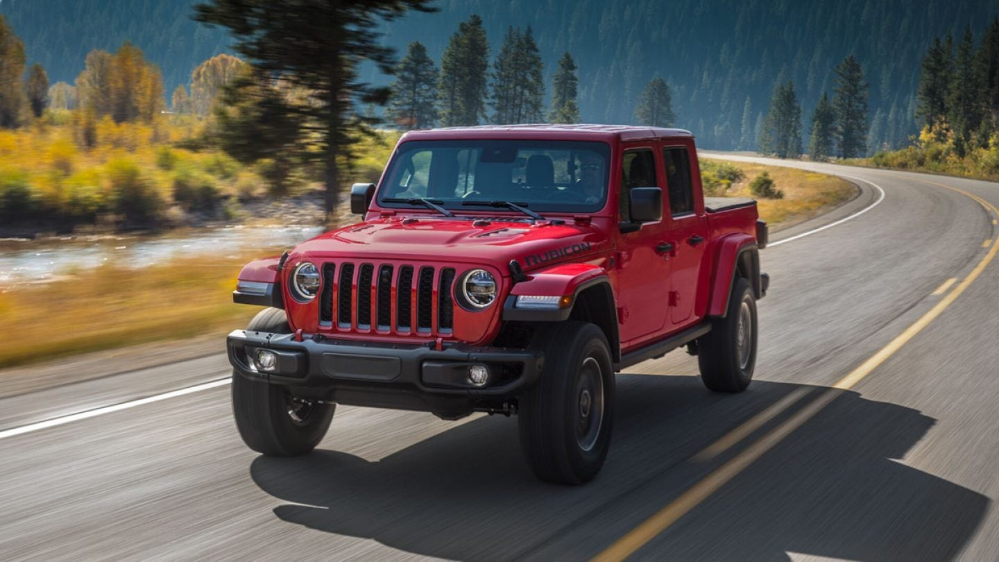 Red Jeep Gladiator Pickup Truck Driving on Road