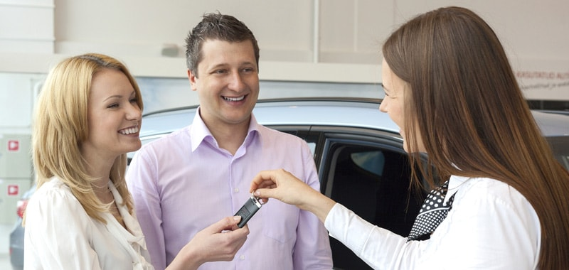 Saleswoman handing new car keys to young couple