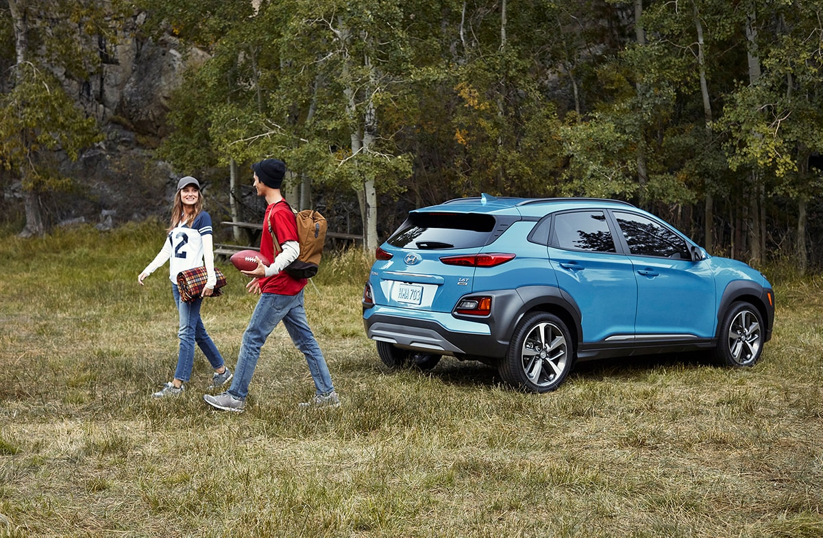 Jack Giambalvo Hyundai is a Hyundai Dealership in York near Lancaster, PA | Young man and woman walking away from 2020 Hyundai Kona parked by the woods