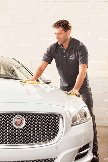 Jaguar service tech washing car after appointment
