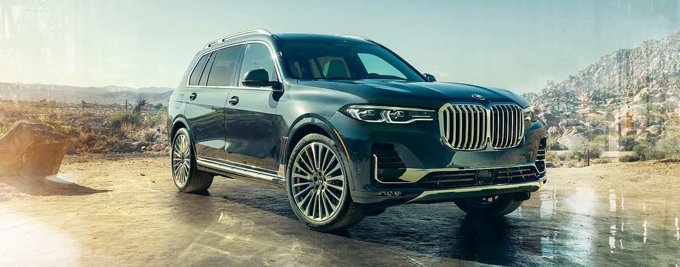 A black 2021 BMW X7 is parked in front of a desert and mountains.