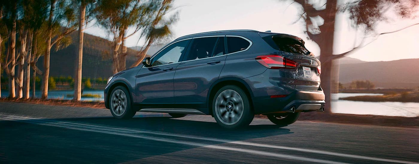 A gray 2021 BMW X1 is shown from the side driving in front of a lake after getting a Cincinnati BMW lease.
