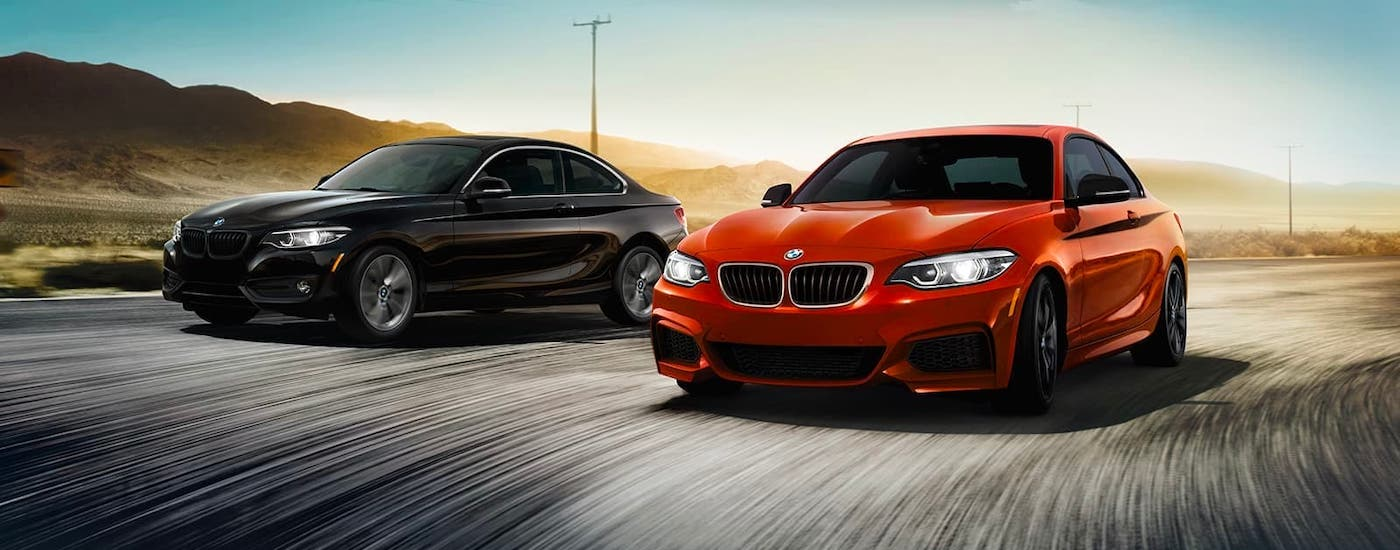 A black and a red 2021 BMW 2 Series are driving on a winding road.