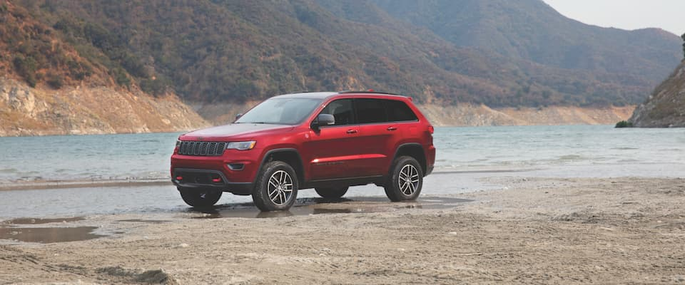 A red Jeep Cherokee parked by a lake