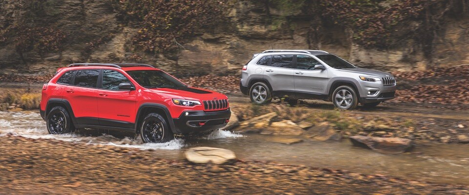A red and a silver Cherokee offroading in a creek