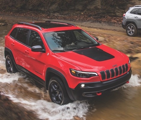 A red 2019 Jeep Cherokee offroading in a river