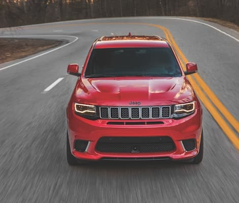 A red 2019 Jeep Grand Cherokee driving down an open road