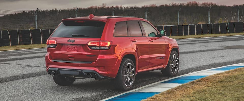 A red 2019 Jeep Grand Cherokee driving on a track