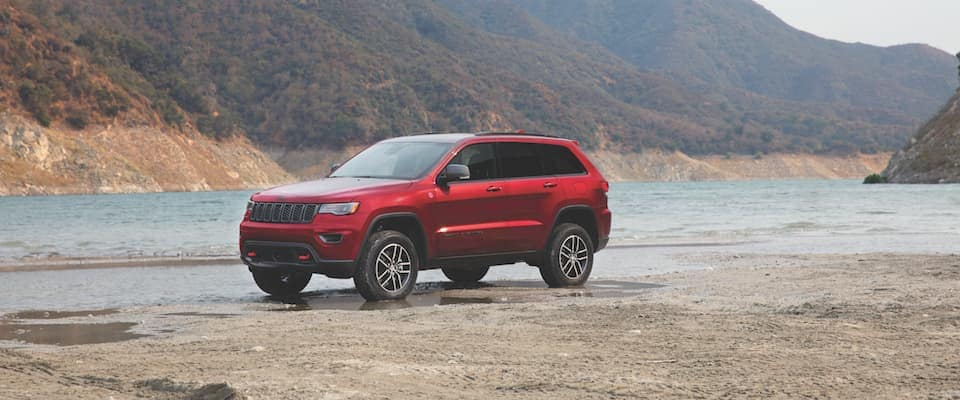 A red 2019 Jeep Cherokee parked near a lake and mountains