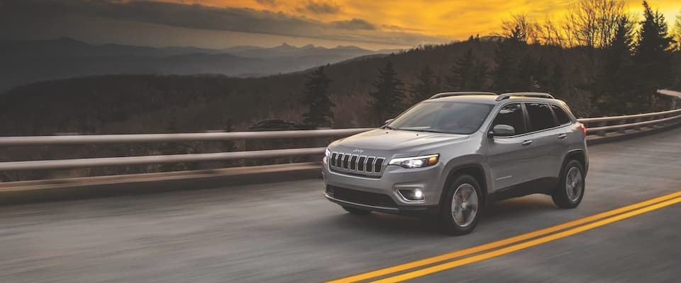 A silver 2019 Jeep Cherokee driving down the road at sunset