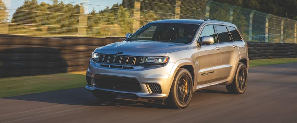 A silver 2019 Jeep Grand Cherokee driving down a track