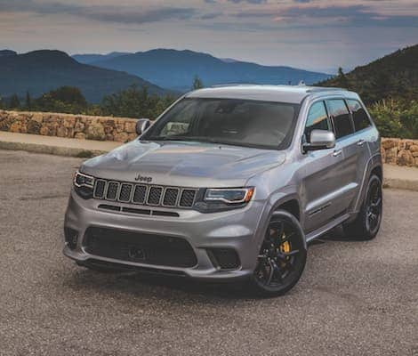 A silver 2019 Jeep Grand Cherokee parked at a mountain overlook