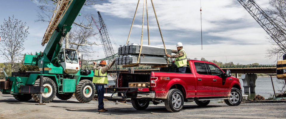 Two construction workers loading steel into a red 2019 Ford F-150