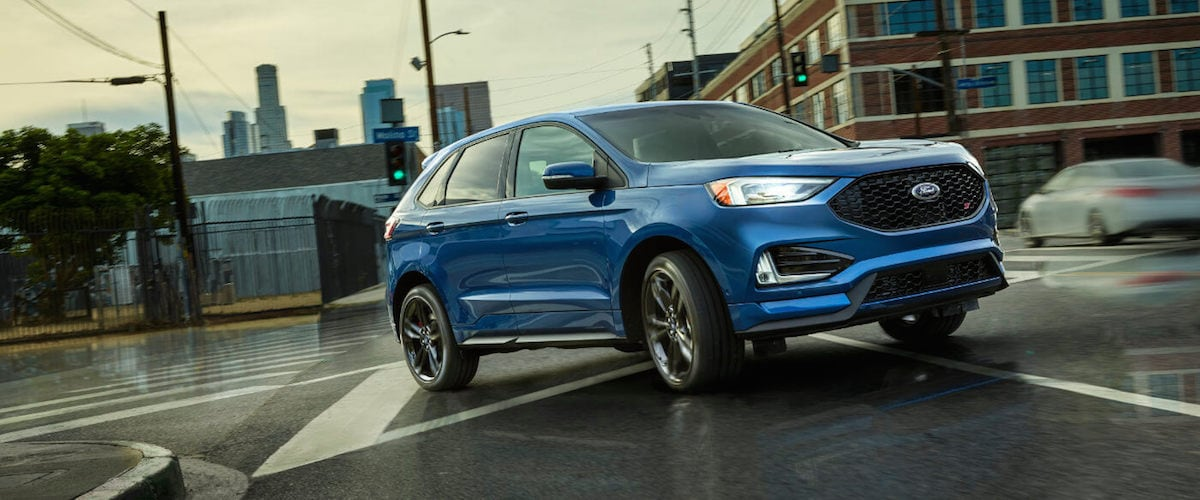 A blue 2019 Ford Edge driving through an intersection in a city