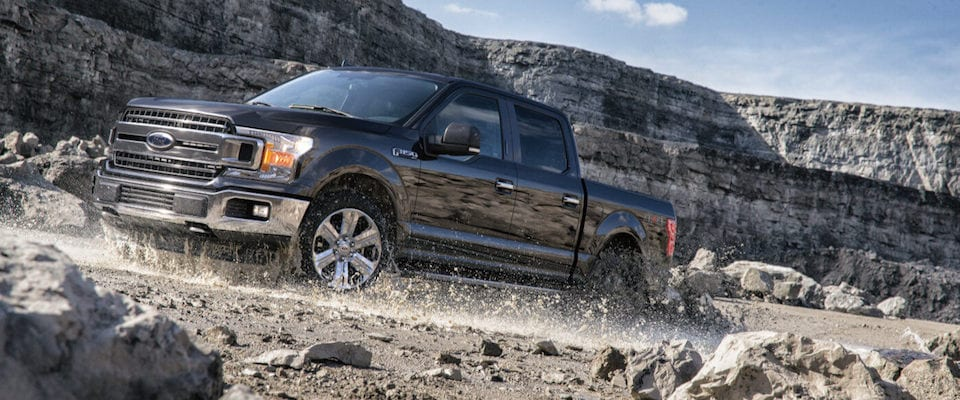A black 2019 Ford F-150 driving through a quarry