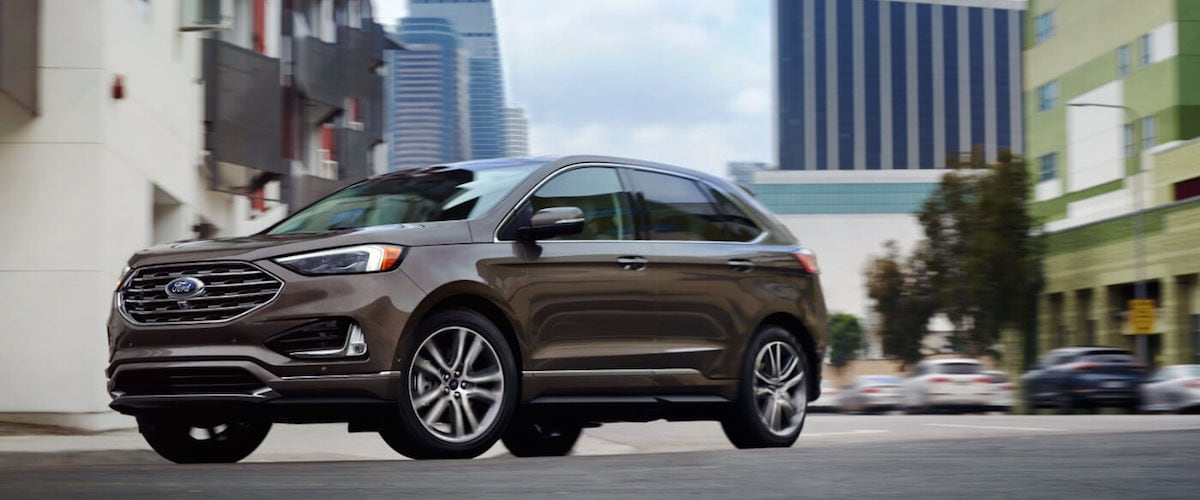 A brown 2019 Ford Edge driving through a city