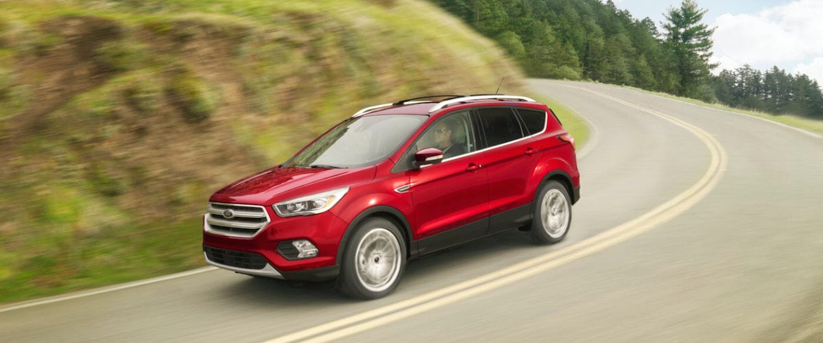 A red 2019 Ford Escape driving down an open road