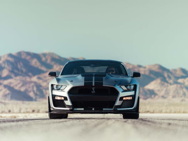 A silver 2020 Ford Mustang driving down an open road away from the mountains