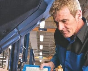 A service technician replacing a cars filters