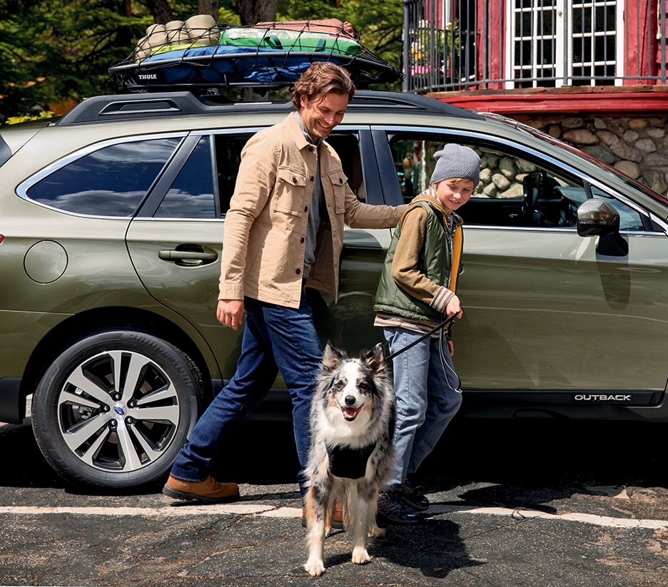 Man and Boy with Dog next to Subaru Outback
