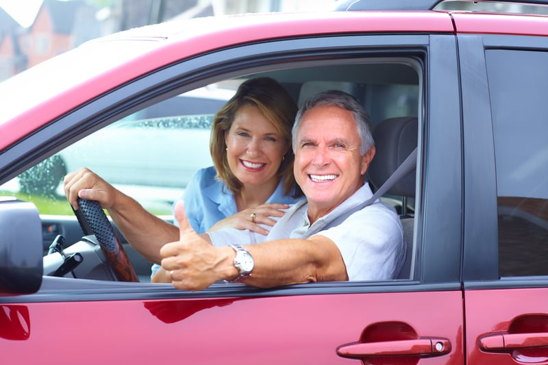 senior couple driving leased car