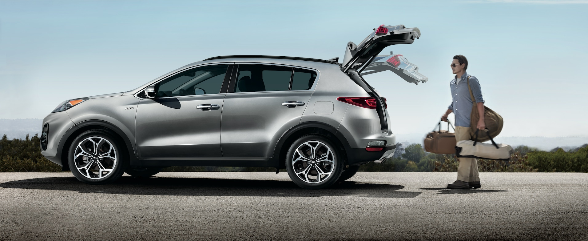 Kia of New Bern is a Car Dealership in New Bern near River Bend, NC | Grey 2020 Kia Sportage being unloaded