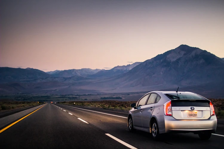 new toyota prius driving down mountainous highway at sunset