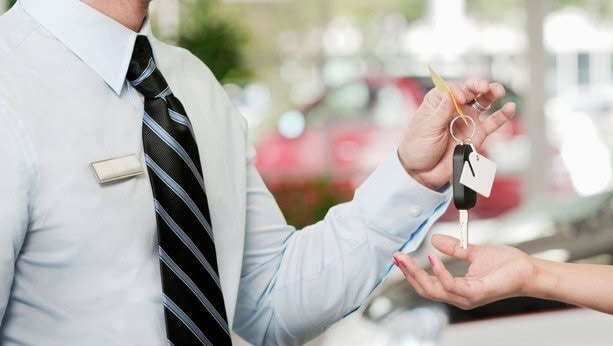 Guy Hands Keys to Happy New Car Owner